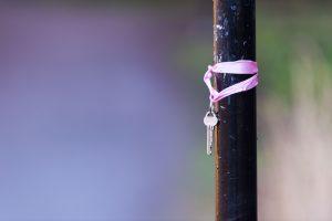 Key on purple string hanging on wood post