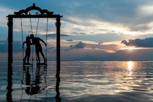 Two people kissing on swings over the ocean